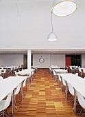 Moderner Speisesaal mit weissen Tischen und 50er Jahre Stuhlklassikern