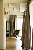 Blick in einen Schlafraum mit schmalem Standspiegel, Designersessel und fliessenden Vorhängen