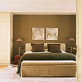 Schlafraum in Naturfarben mit Doppelbett und gepolsterter Sitzbank