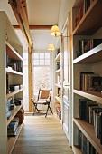 Flur mit Bücherwänden und Klappstuhl vor großem Fenster