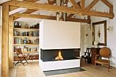 Gemütlicher Wohnraum mit offenem Dachstuhl, Kaminfeuer und Bücherwand
