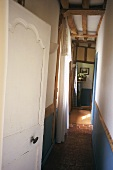 View along narrow hallway with wood-beamed ceiling and potted plant on pedestal in corner