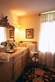 Traditionelles Badezimmer mit Holzkommode als Waschtisch, großem, gerahmten Spiegel, Teppich mit floralem Muster und blickdichtem Fenstervorhang mit Spitzenbesatz