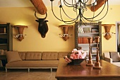 Living room with massive ceiling beams, bulls head, vase-shaped wicker wall lamps and delicate iron chandelier above wooden table with flower arrangement