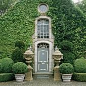 Üppig begrünte Hausfassade mit Eingangstür, dekorativen Steinpokalen und einem Spalier von Buchsbaumkugeln