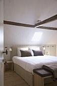 Heller Schlafraum mit Dachluke in der Dachschräge und Deckenbalken; darunter Doppelbett mit gepolstertem Kopfende