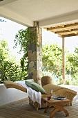 Korbliege auf der überdachten Holzterrasse mit Natursteinstützen und Bambusmatten als erweiterten Sonnenschutz