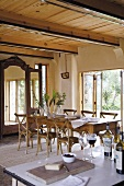 Long dining table and chairs in front of cupboard with mirrored doors and open French windows leading to terrace and garden