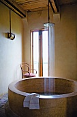 Round, unconventional stone bathtub with water falling from large rainfall shower head