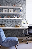 Blue patterned easy chair in front of workspace with patterned wallpaper, floating shelves and desk