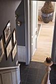 Aufsicht auf einen Flur mit Bildersammlung, brennende Kerze auf dem Treppenpfosten und einem Pflanzentopf