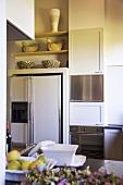 weiße Küche mit einzelnen Edelstahlfronten und Küchenregal mit dekorativen Tierfiguren und Schüsseln aus Holz