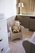Kleiner Kinder-Korbstuhl mit einem Teddybär