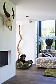 Detail of living room with open fireplace, animal skull and patterned couch with scatter cushions