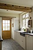 Küche mit Fenstertür, Terrakottafliesen und rustikalem Deckenbalken