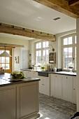 Sonnige Küche mit schweren Deckenbalken, Terrakottafliesen am Boden und weisse Holzschränke