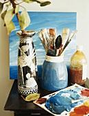 Malutensilien und eine Vase auf dem Beistelltisch
