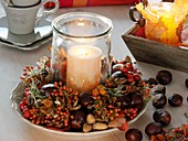 Candle in glass in wreath of rose hips, chestnuts and acorns