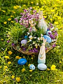 Flowers and Easter Bunny in Easter basket in field of dandelions