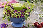 Candle in wreath of asters and other flowers in enamel colander