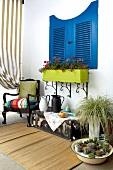 Blauer Fensterladen und Möbel davor