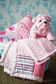 Pink blankets, cushion & cuddly plush dog in basket