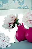 Mirror with the word 'gorgeous', flower in vase
