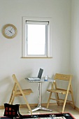 Small table with laptop and two folding chairs