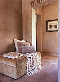 Seating area with upholstered stool, cushions, throw and tray