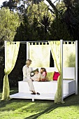 Mother and daughter sitting on day bed in garden