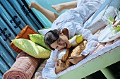 Young woman on bed with dessert and drink