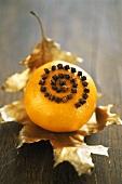 Orange studded with cloves on gilded holly leaf