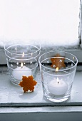 Zwei Windlichter und Sterne aus Orangenschale auf Fensterbank
