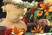 Bust with rose hip wreath & floral decorations in warm colours