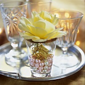 Festive decoration: tiny parcel, beads & yellow rose in glass