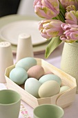 Coloured Easter eggs in a small basket with vase of tulips