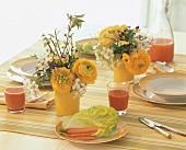 Gedeckter Tisch mit Sträusschen aus Ranunkel und Hornveilchen