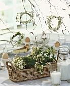 Basket & wreaths of flowering twigs as table decoration