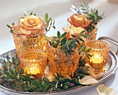 Small vases with roses, pistachio foliage & candles