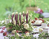 Flower wreath with candles on table laid for coffee