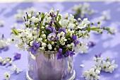 Strauss von Veilchen und Blütenzweigen in einer Dose