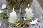 Two burning windlights and wild strawberries