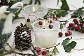 Frosted glasses with candles, cones and haws
