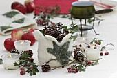 Winterliche Tischdeko mit Kerzen, Zapfen, Zieräpfel und Filz