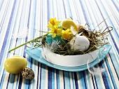 Verschiedene Eier im Osternest mit Narzissen und Heu