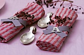 Two fabric napkins with napkin rings and elderberries