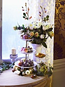 Sugared fruit on tiered stand and flowers by window