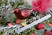 Red glass bird on conifer branch with Christmas greeting