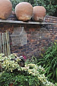 Green plants and terracotta pots on a garden wall