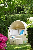 A luxurious roofed wicker beach chair with a side table in a garden